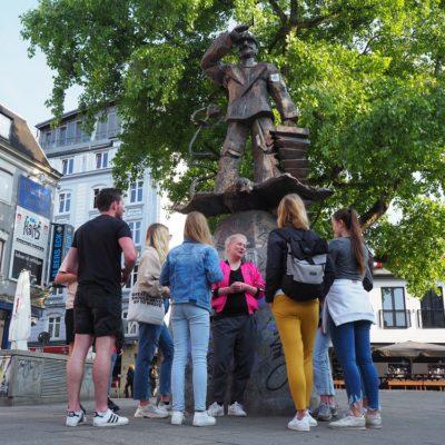 Die Schülergruppe macht während des Stadtteilrundgangs halt auf dem Hans-Albers-Platz. Von Tourguide Dani erfahren die Schüler*innen viel über die Geschichte des Platzes und das alltägliche Leben auf St. Pauli.