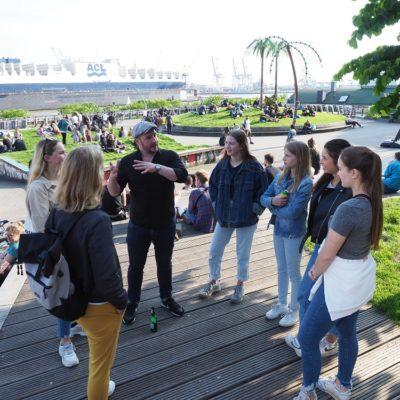Schülerinnen und Lehrerin lassen sich von unserem Guide vor Ort die Geschichte zum Park Fiction erklären.